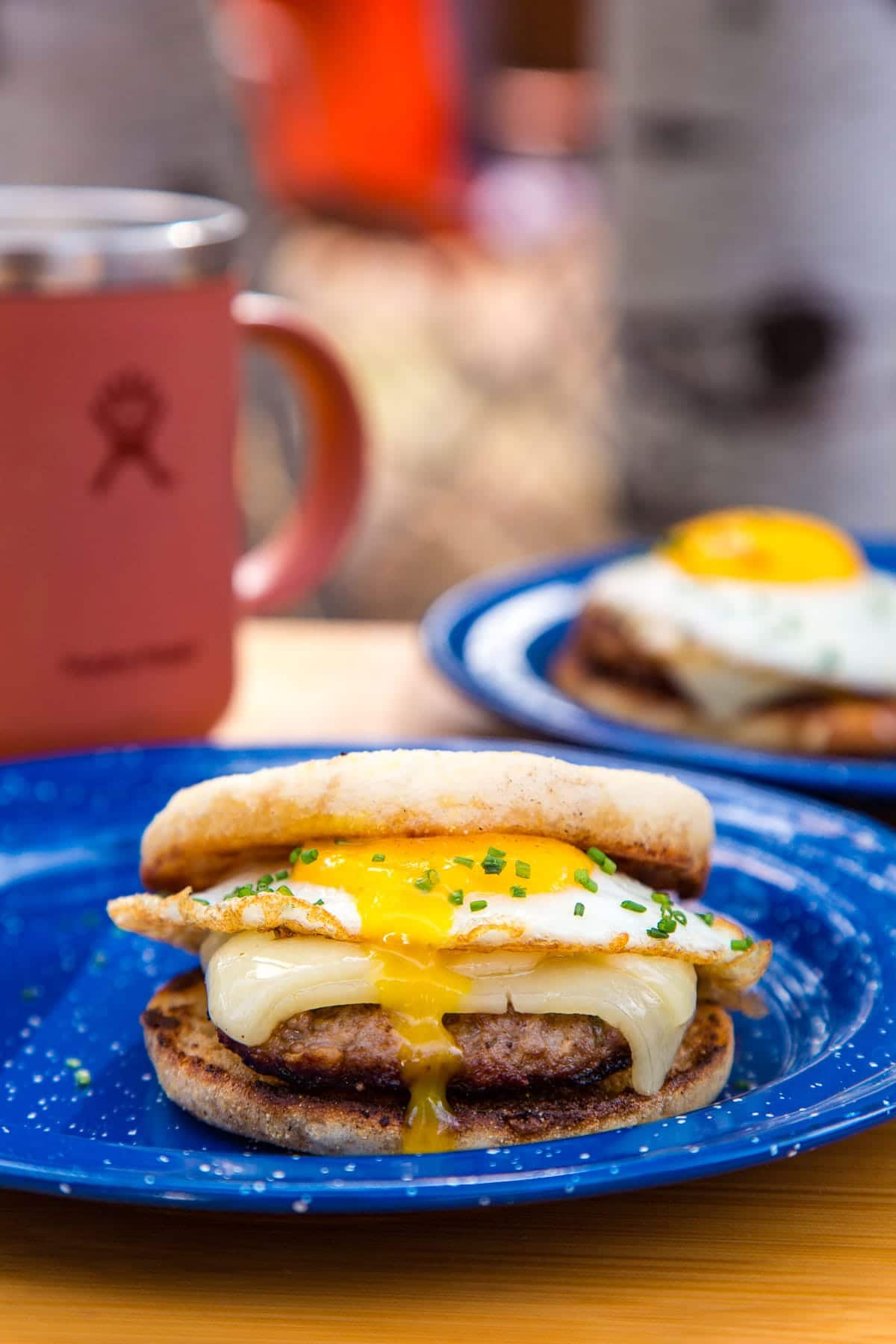 Side view of a sausage and egg sandwich with a runny yolk.