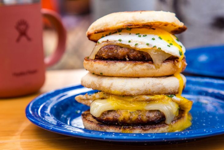Side view of two sausage and egg sandwiches with runny yolks.