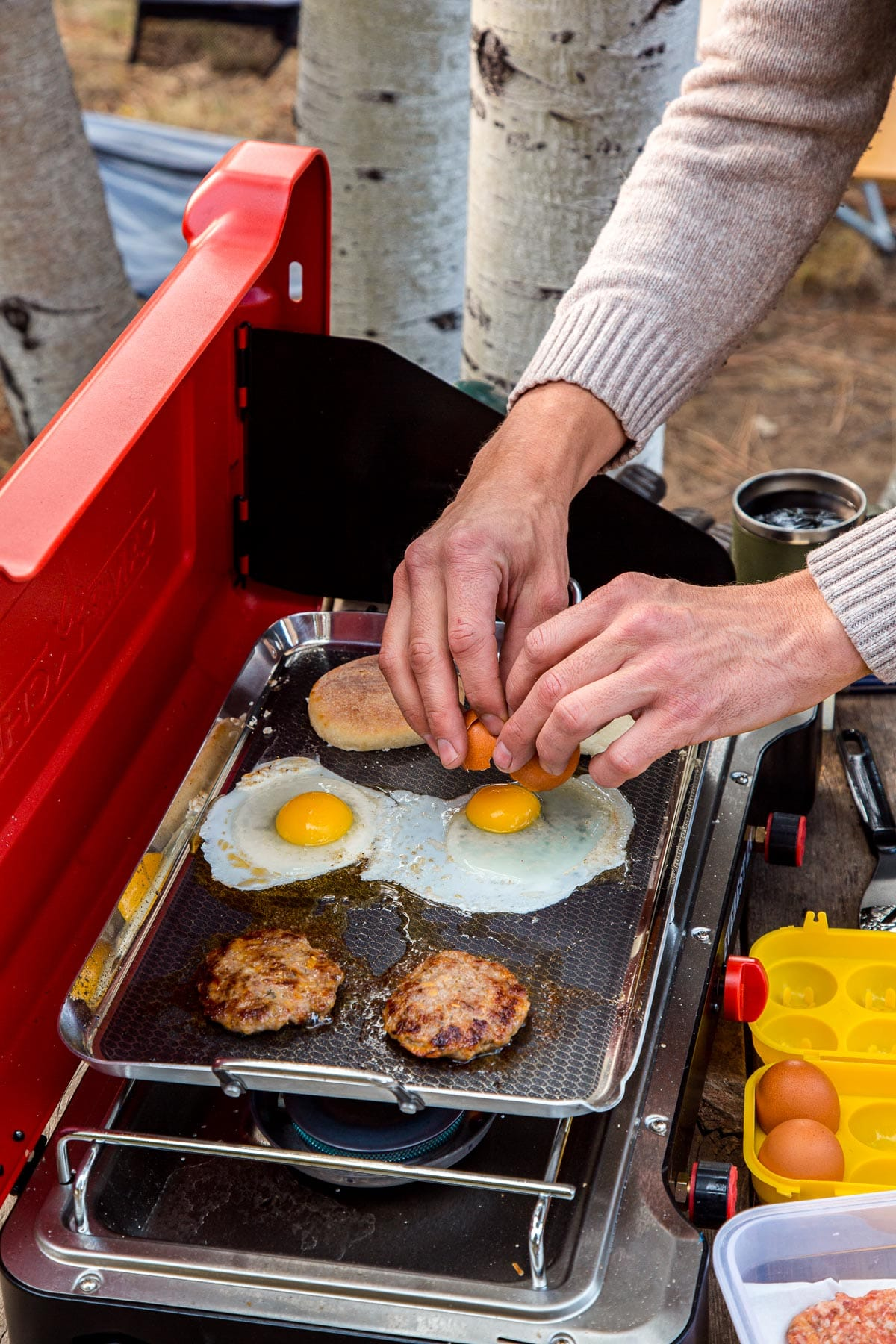 Michael is cracking an egg onto a griddle on a camp stove.