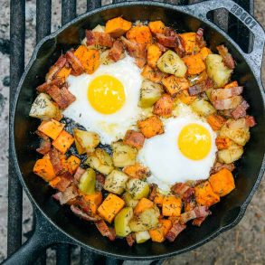 Overhead view of apple and sweet potato hash with two fried eggs in a cast iron skillet over a campfire.