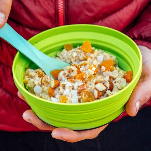 Man holding a green backpacking bowl full of apricot ginger oatmeal
