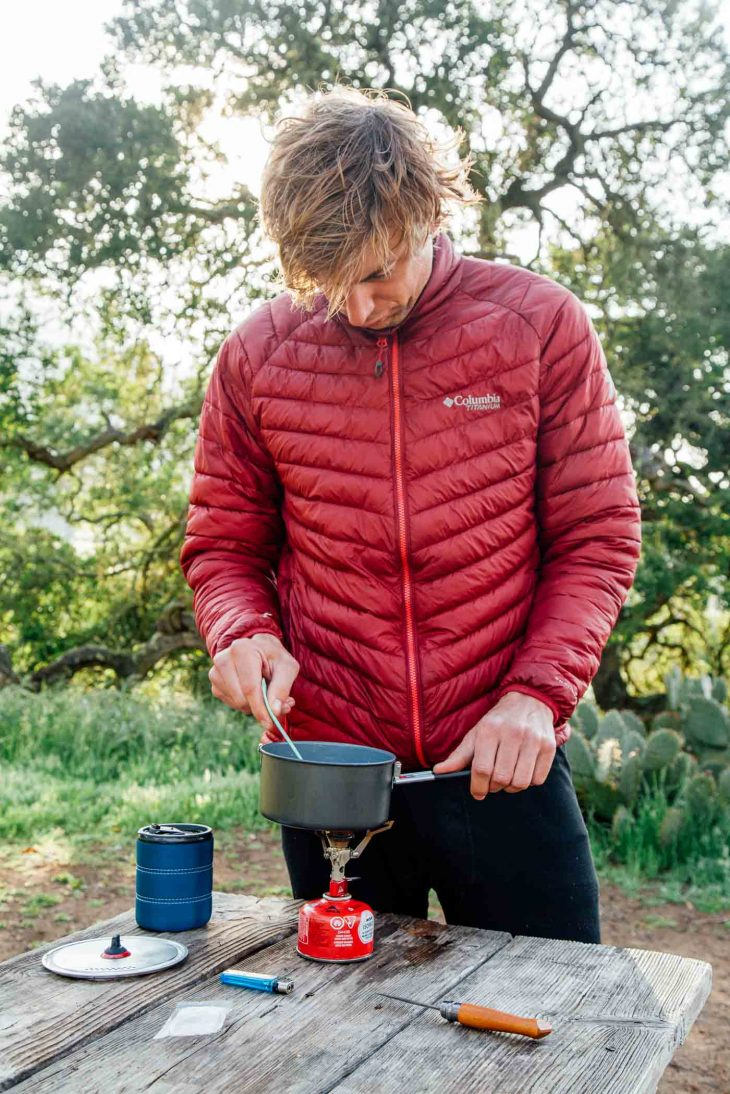 Michael standing at a camp table stirring a pot on a backpacking stove.
