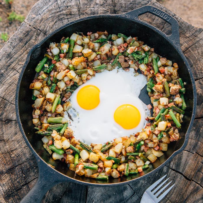 Potatoes, asparagus, and two eggs in a skillet on a stump