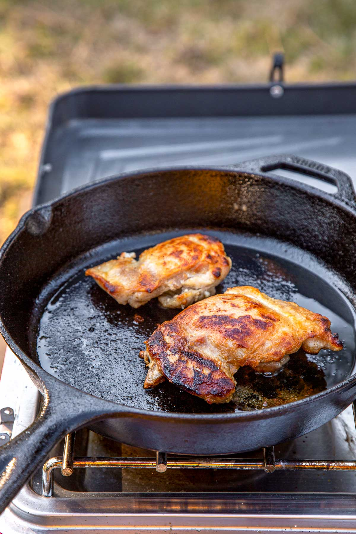 Two browned chicken thighs in a cast iron skillet on a camping stove.