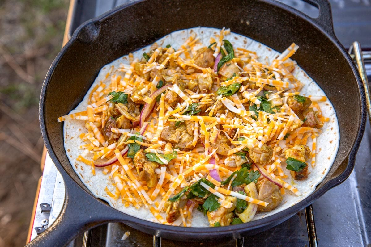 A tortilla topped with BBQ chicken and cheese, in a cast iron skillet.