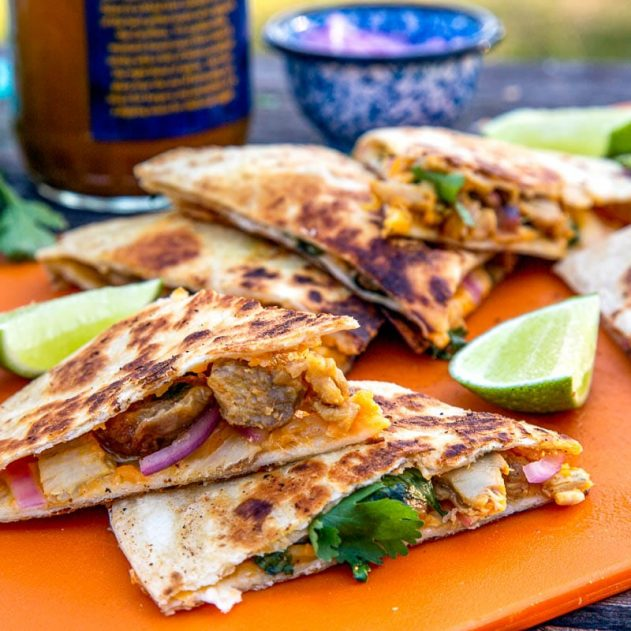 Sliced quesadillas stacked on an orange cutting board.