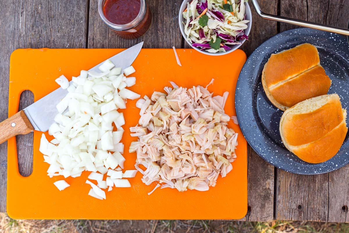 Chopped onions and jackfruit on an orange cutting board