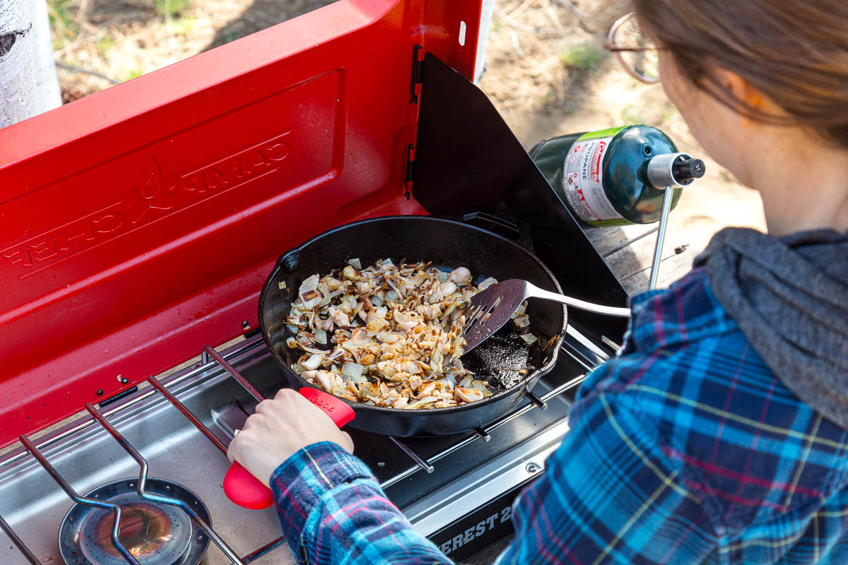 Megan cooking jackfruit in a skillet on a camping stove
