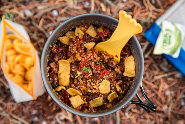 A backpacking pot filled with a burrito bowl backpacking meal