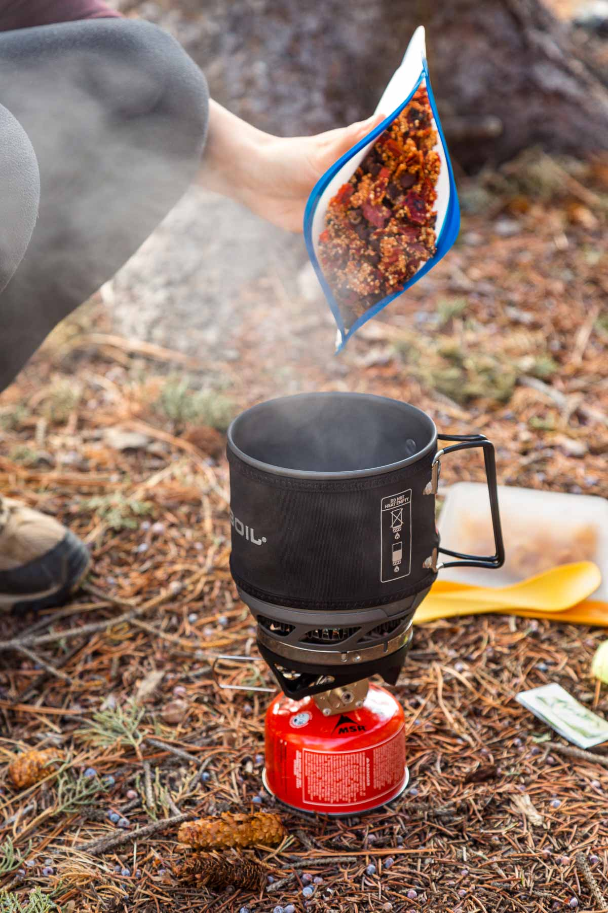 Megan pouring a backpacking meal from bag into a Jetboil stove
