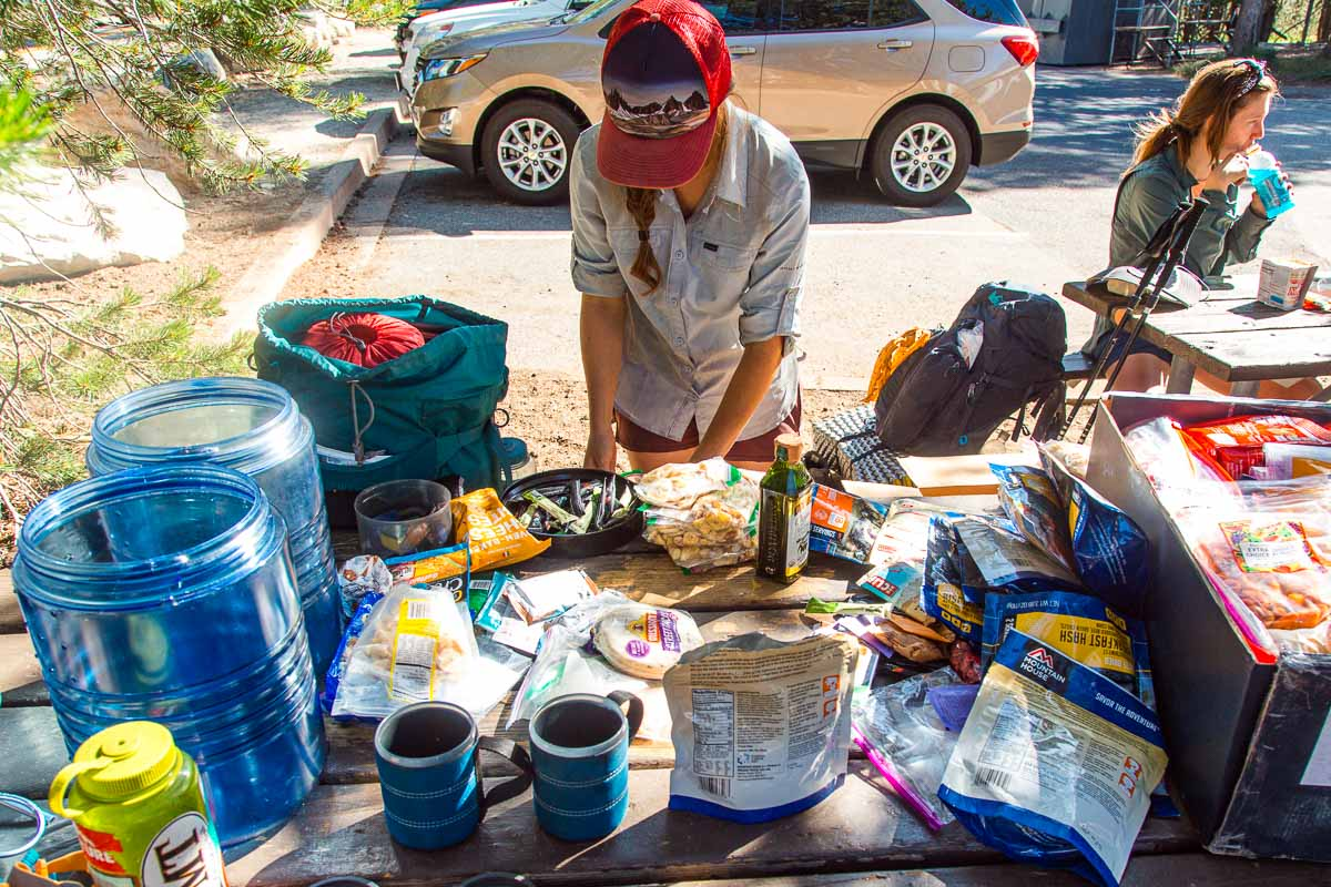 Megan sorting through backpacking food that is spread out on a picnic table