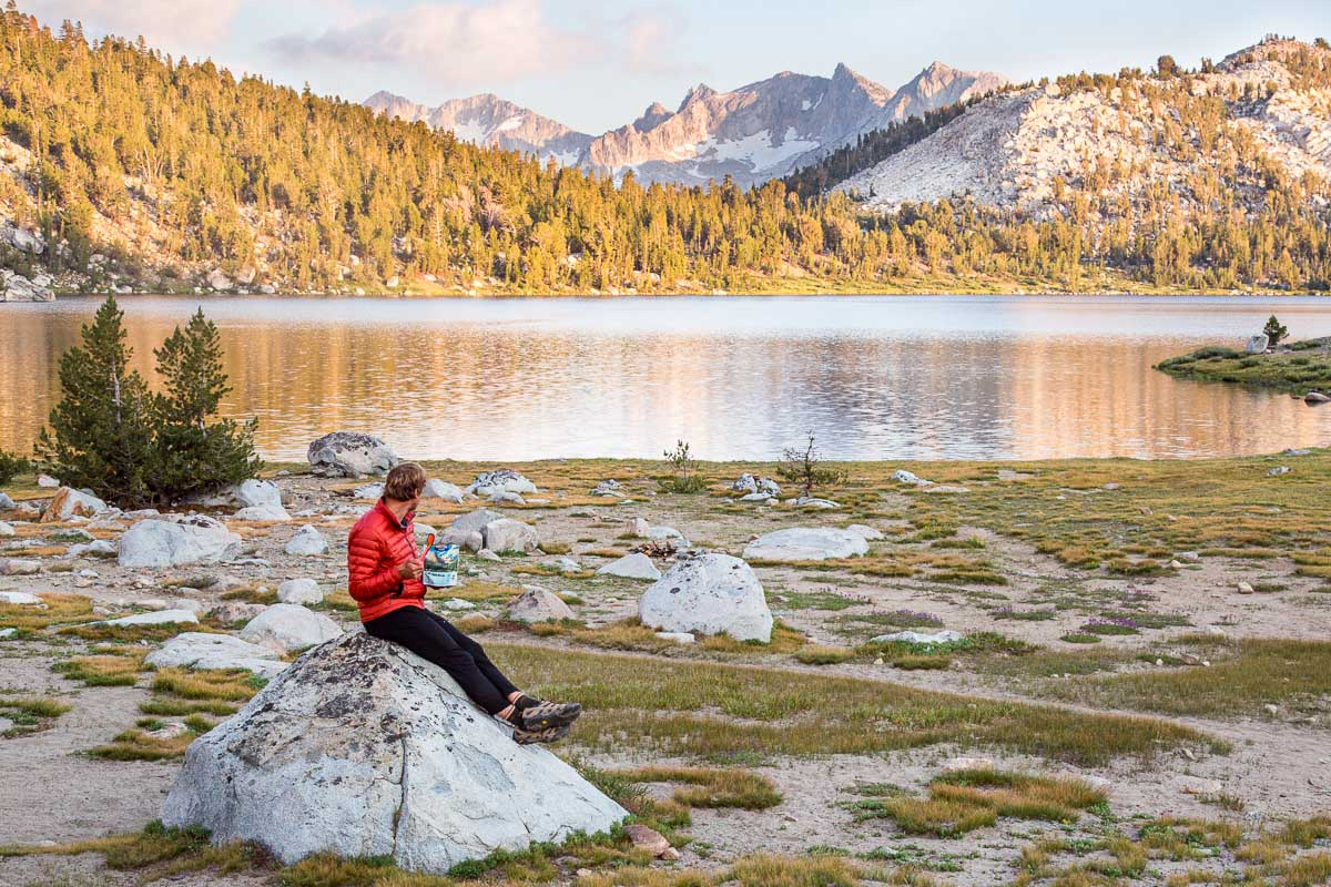 Michael sitting on a rock in front of a lake eating a backpacking meal