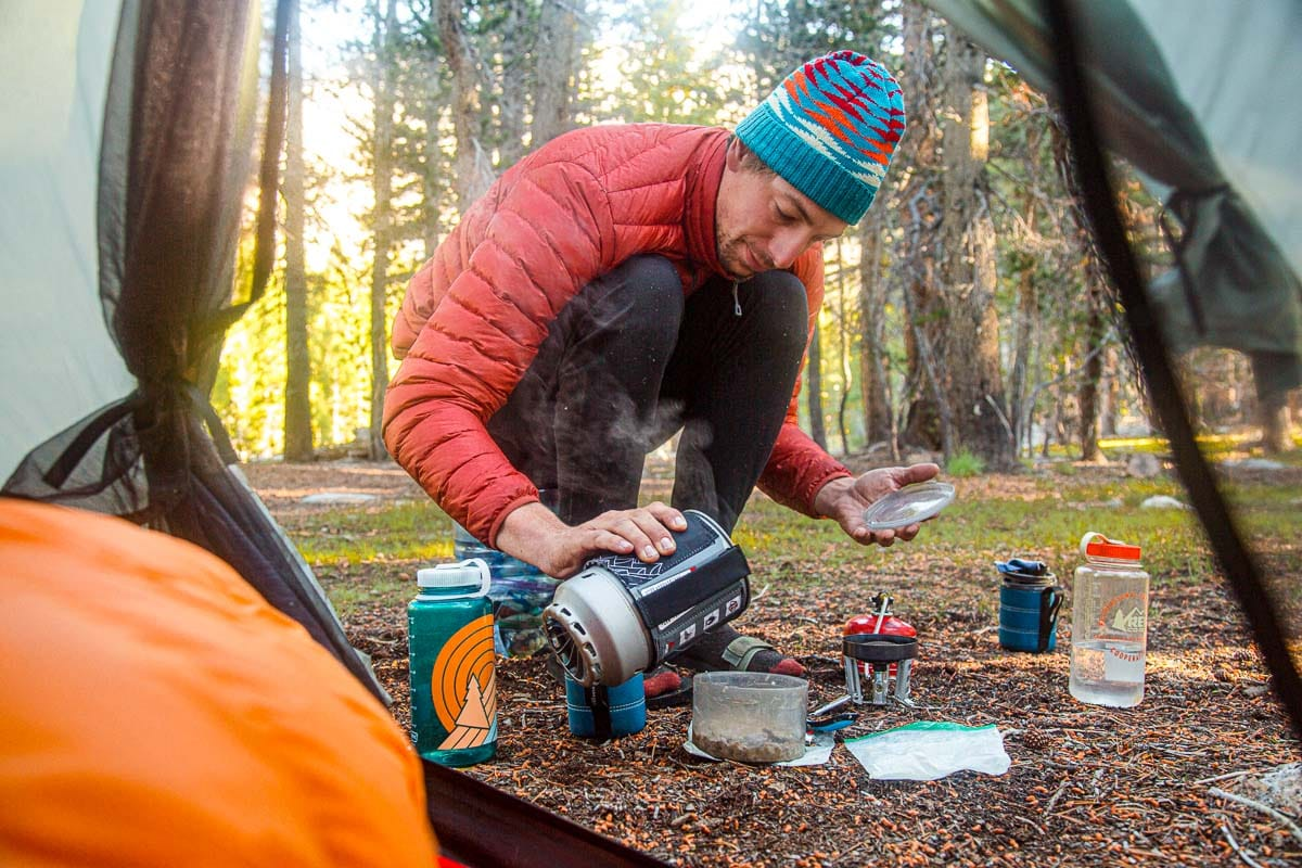 Michael is crouching at a campsite and pouring water from a JetBoil into a cup