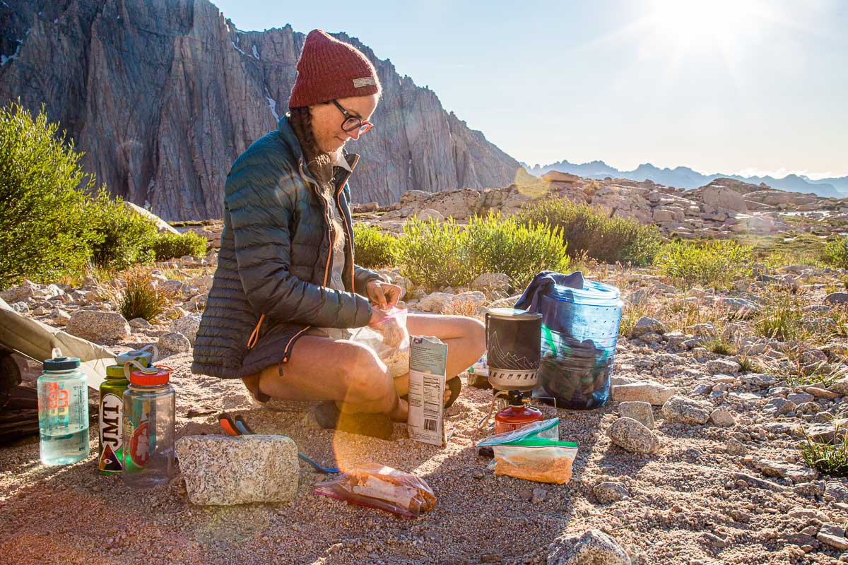 Megan sitting with her backpacking cooking gear at a campsite with mountains in the background