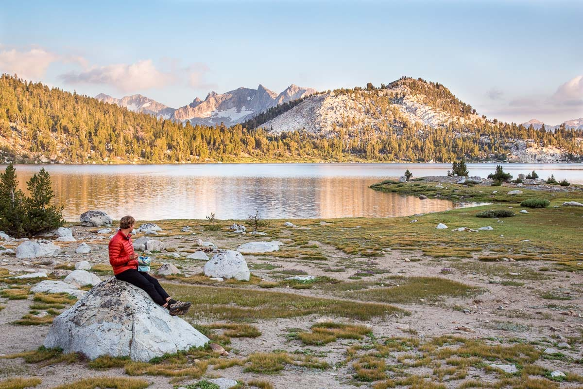 Michael sitting on a rock with a lake and mountains in the background