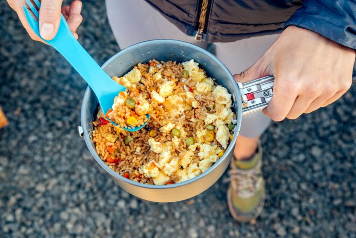 Megan holding fried rice in a backpacking pot