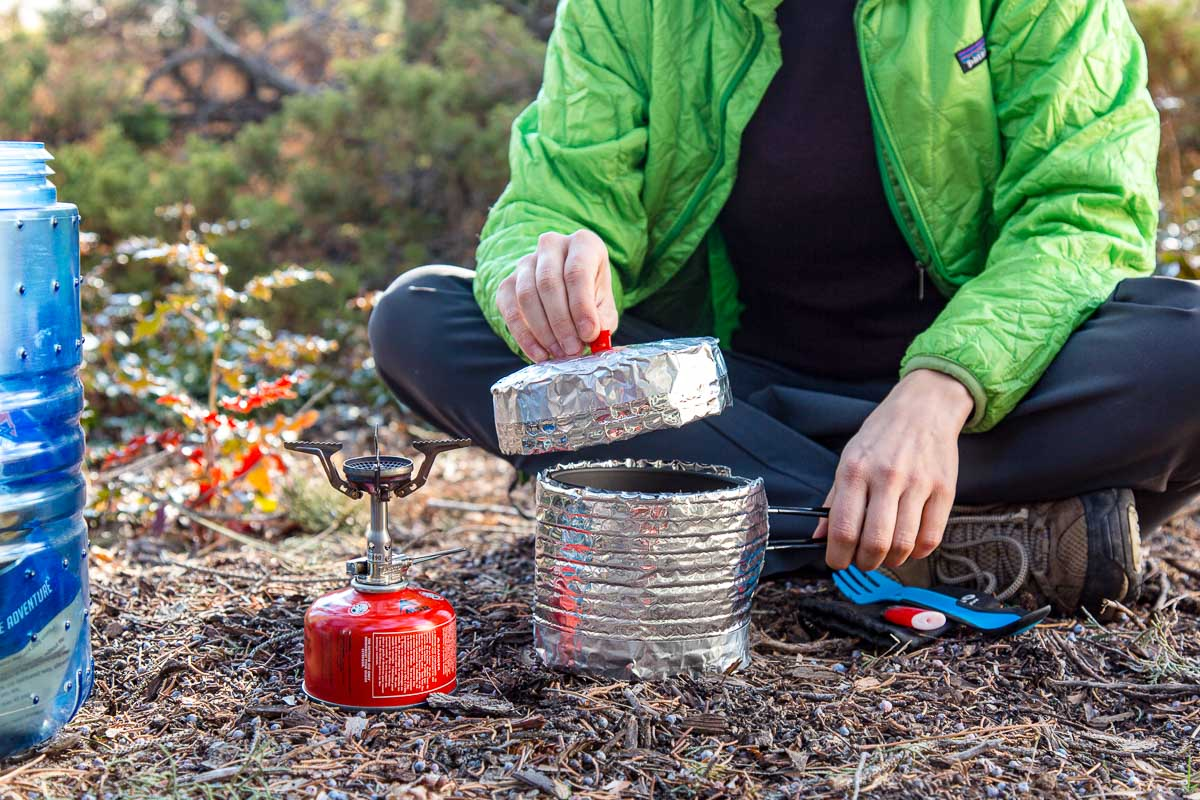 Megan is sitting on the ground outdoors placing the lid on a backpacking pot that is in a cozy