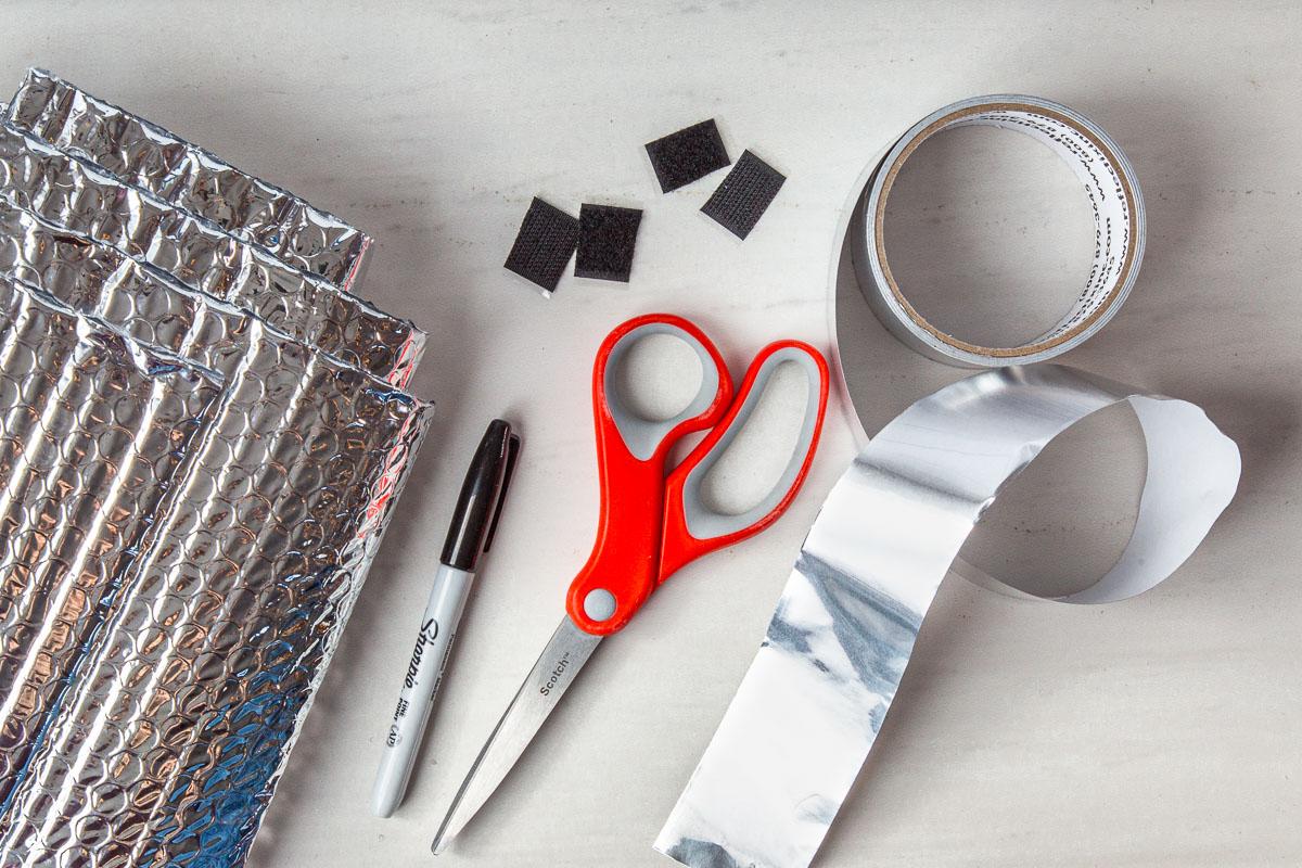 Materials for a pot cozy laid out: reflictix, foil tape, sharpie, scissors, velcro