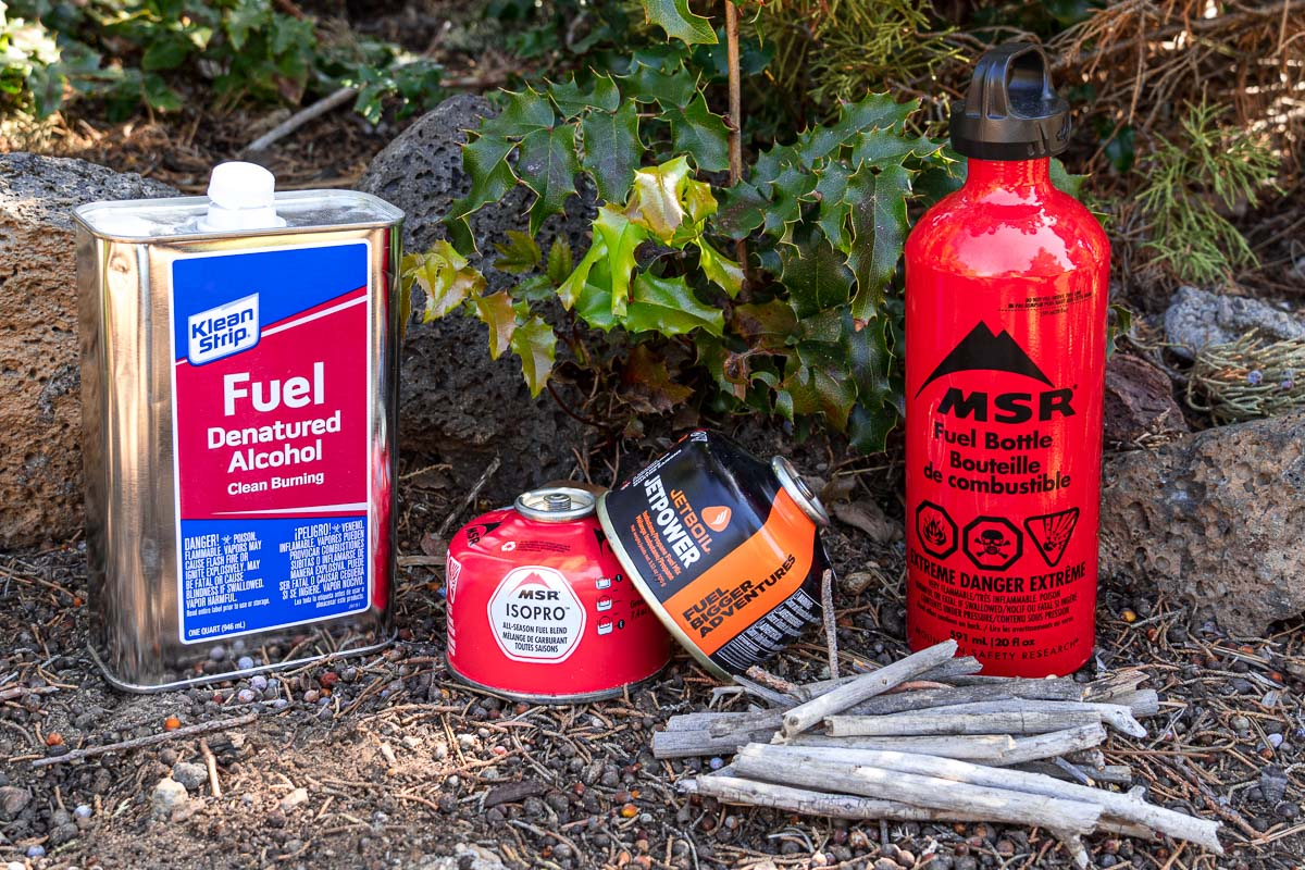 Backpacking fuel bottles: Denatured alcohol, isobutane canisters, and a red liquid fuel bottle