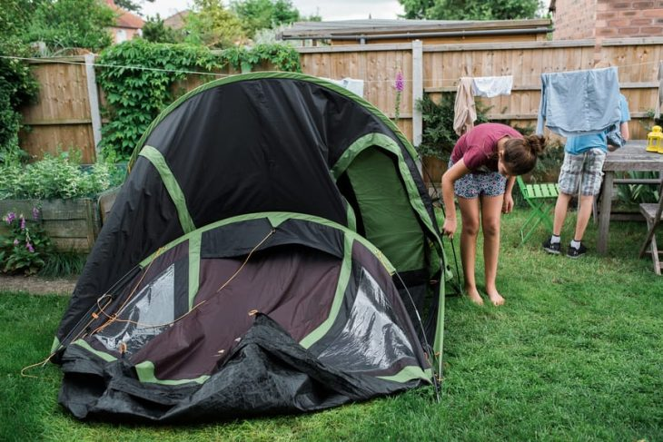 A girl setting up a tent in the backyard