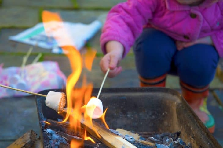 A child roasting a marshmallow over a firepit.