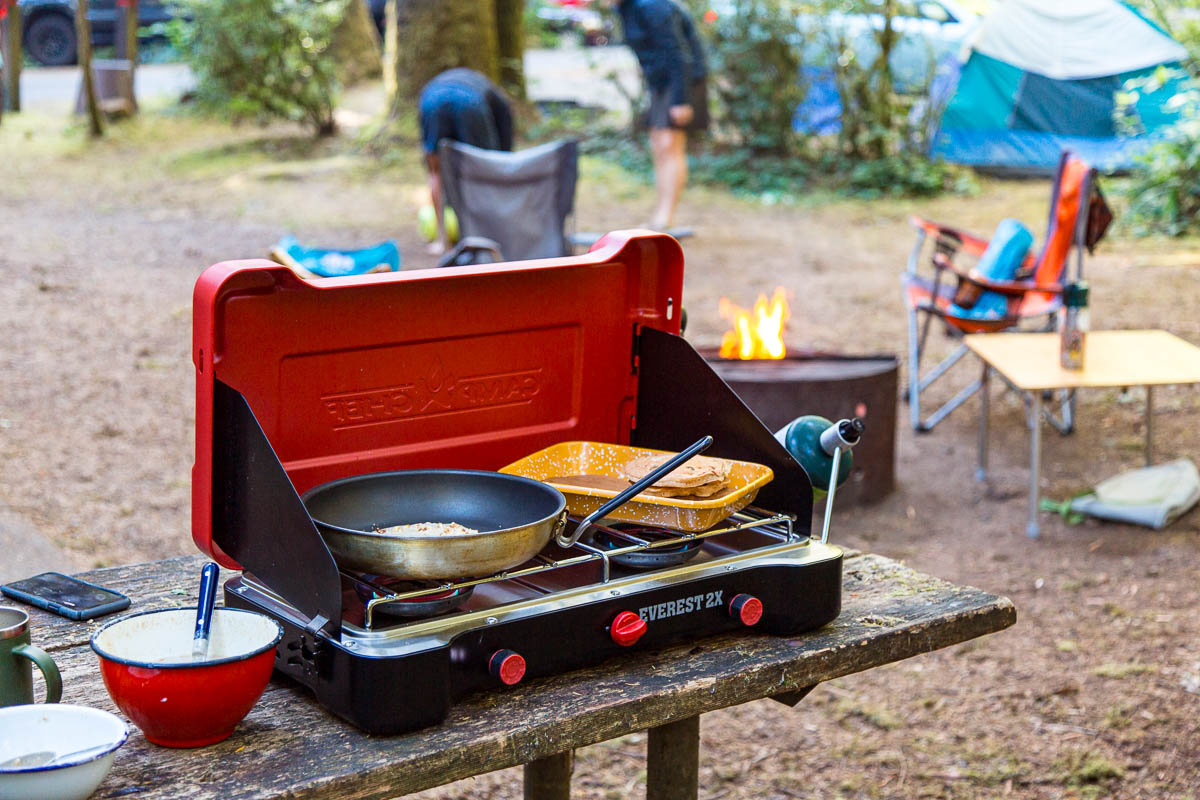 Skillet on a camp stove with a camping scene in the background.