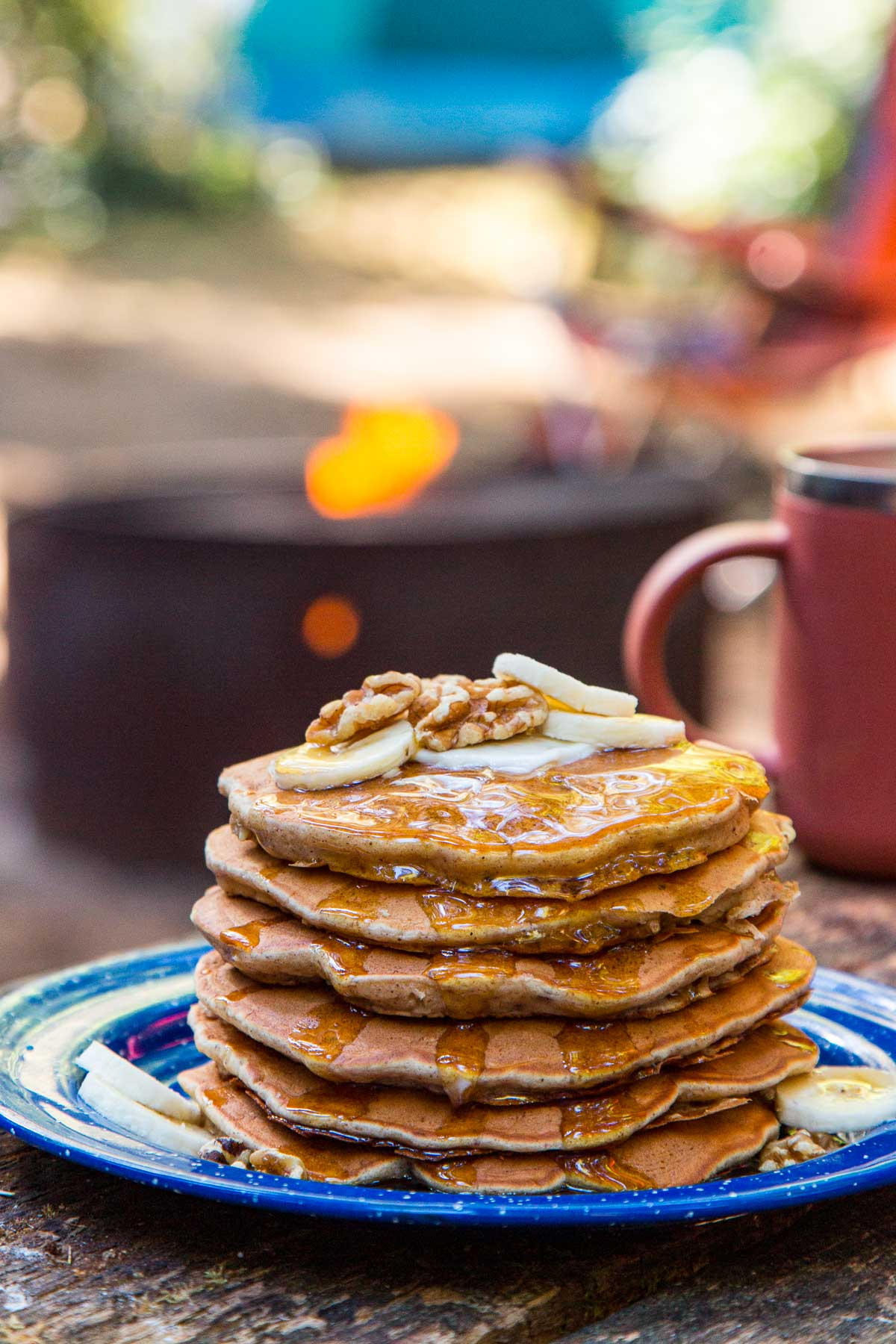 A stack of pancakes on a blue plate, topped with slices of bananas and walnuts and a camping scene in the background.