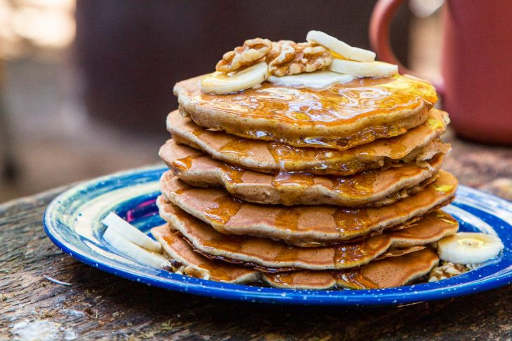 A stack of pancakes on a blue plate, topped with slices of bananas and walnuts.