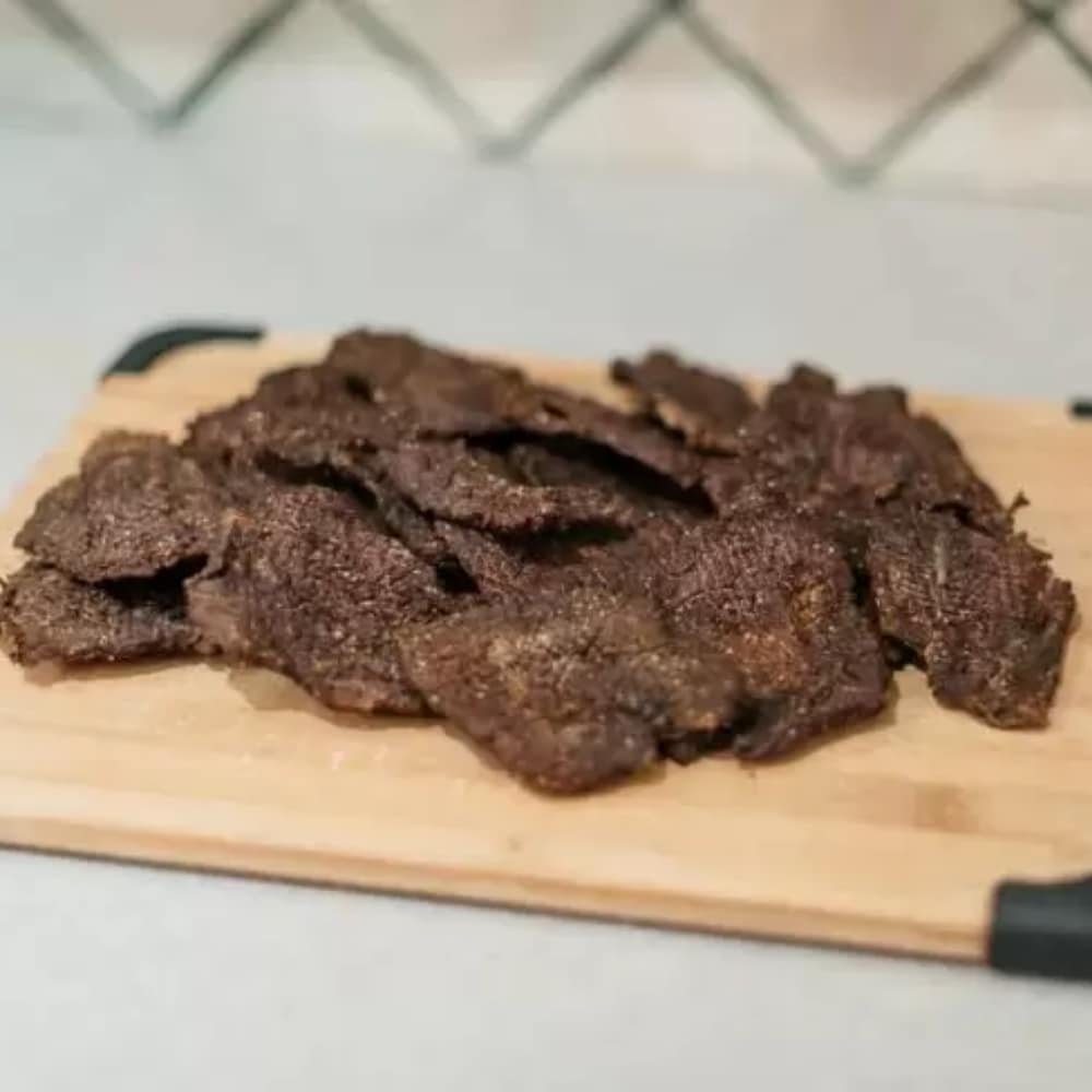 A pile of beef jerky on a wood cutting board