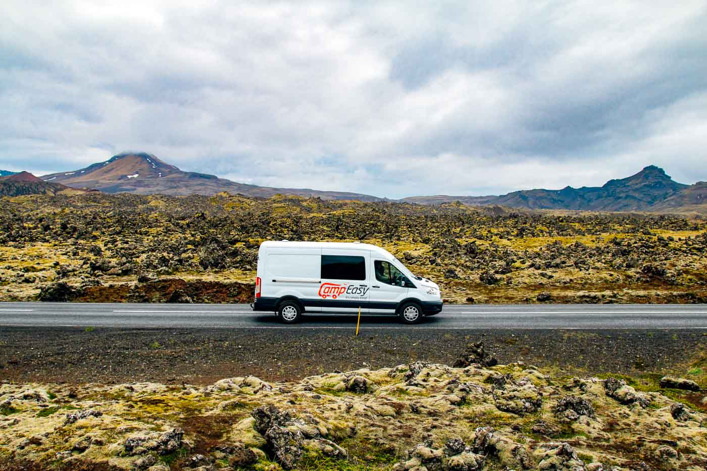 A campervan on a road in front of a lava field covered in moss on Iceland's Snaefellsnes Peninsula.