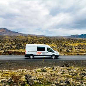 White camper van driving passed the Berserkjahraun Lava Fields in Iceland