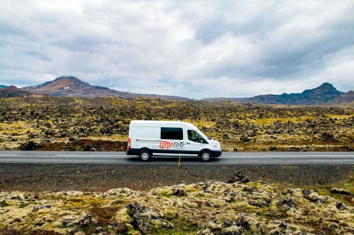 White camper van driving passed the Berserkjahraun Lava Fields in Iceland