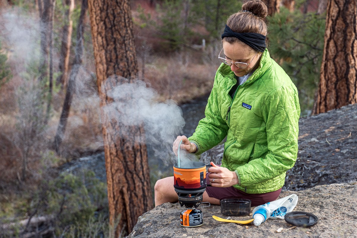 Megan is sitting on a rock cooking over a Jetboil backpacking stove