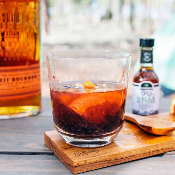 A cocktail in a clear class with a bottle of bourbon and camping scene in the background