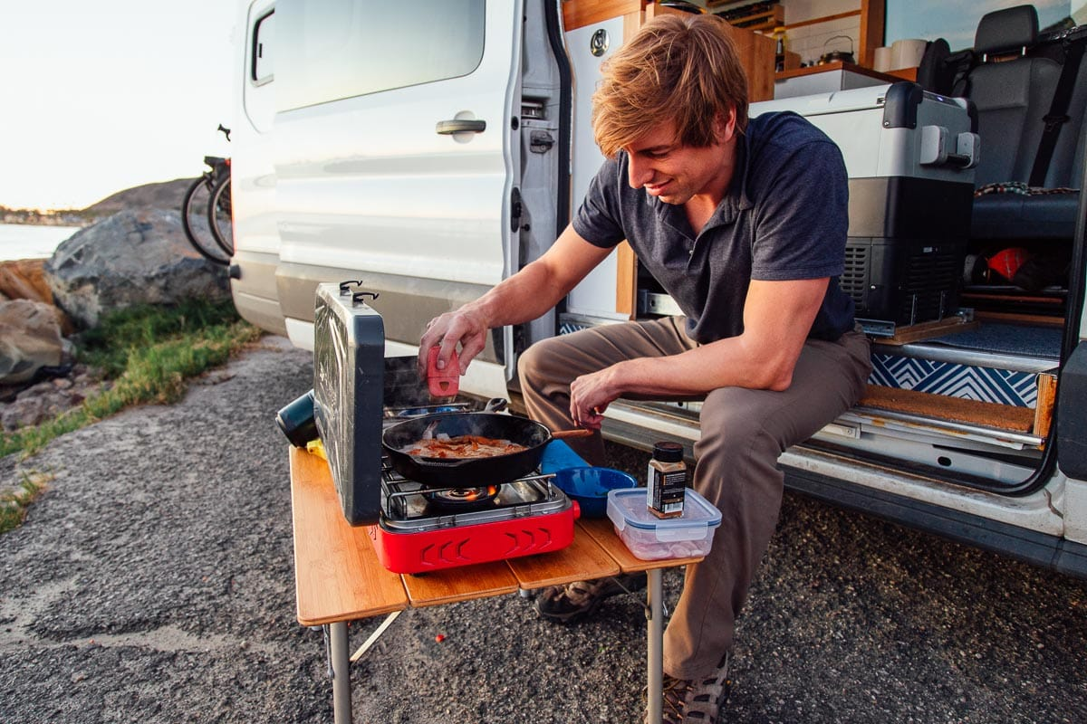 Michael sits on the stoop of a campervan and cooks at a campstove.