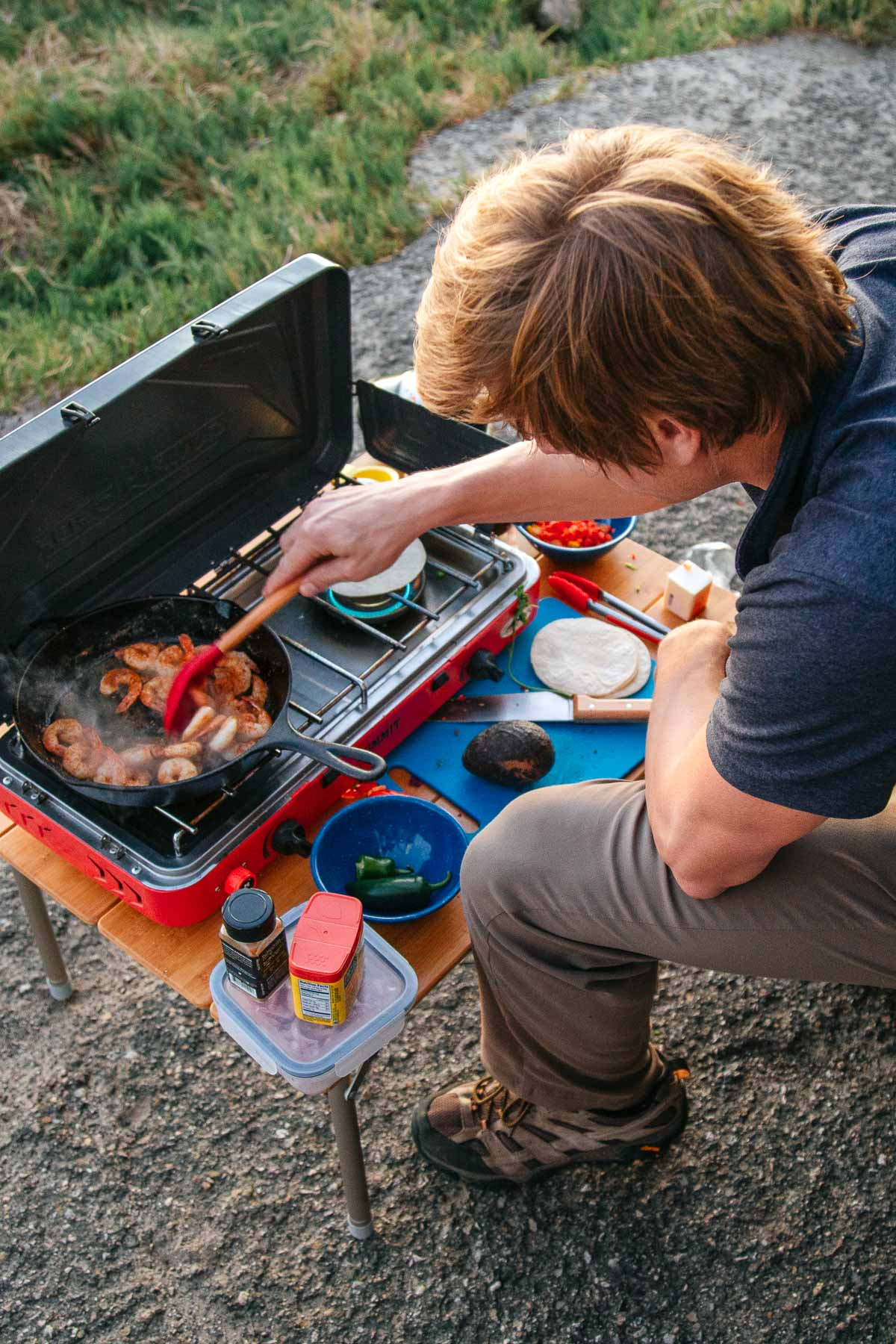 Michael cooking shrimp in a cast iron skillet on a camp stove.