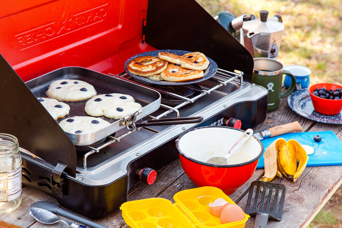 Pancakes on a griddle over a camp stove with various camp cooking utensils in frame