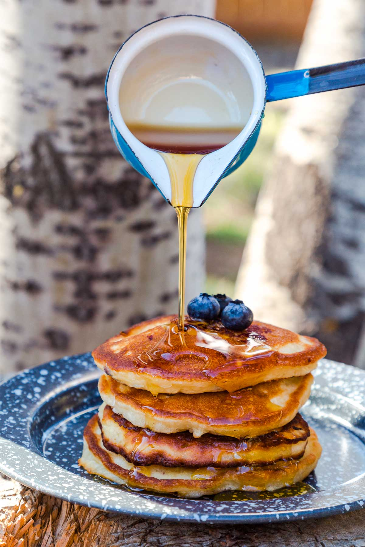 Pouring maple syrup over a stack of blueberry banana pancakes
