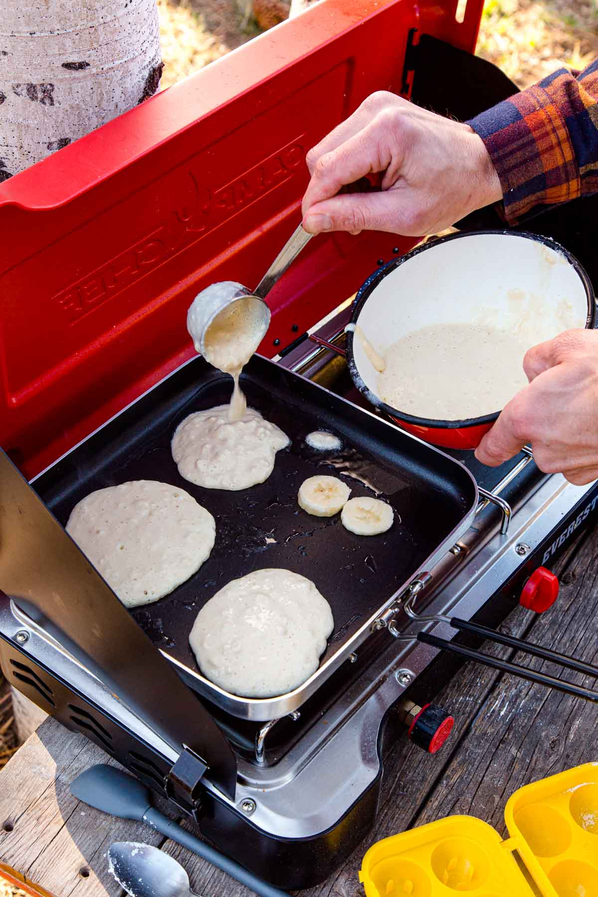 Michael adding pancake batter to a griddle on a camping stove
