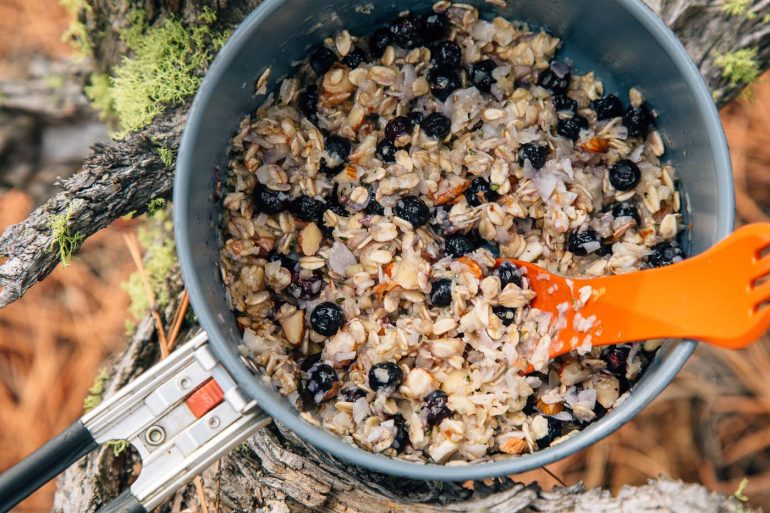 Blueberry coconut oatmeal in a backpacking pot set on a natural background.