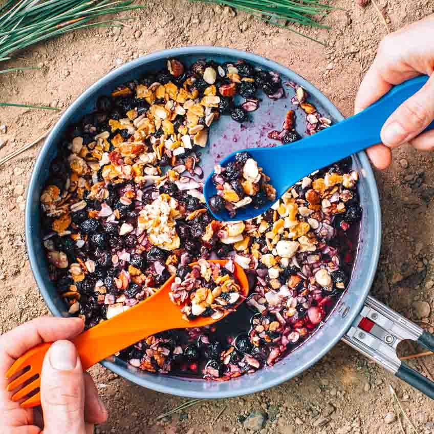Blueberries topped with granola in a skillet with two hands and spoons reaching in