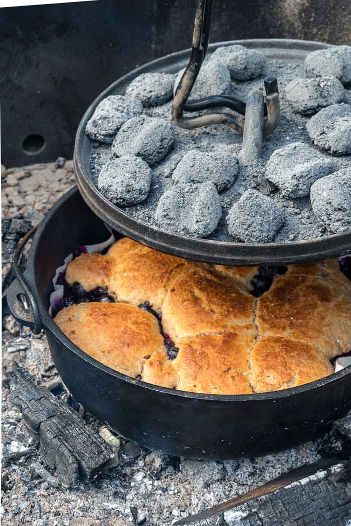 Lifting a dutch oven lid to reveal cobbler