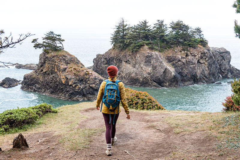 Megan walks on a dirt path towards the edge of a bluff with sea stacks in the distance.