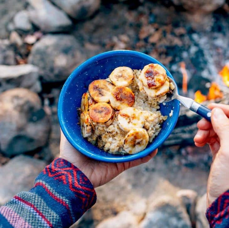 Megan holding a blue bowl of oatmeal topped with bananas and campfire in the background