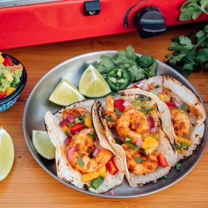 Three shrimp tacos on a silver plate with sliced limes and a small bowl of guacamole on the side.