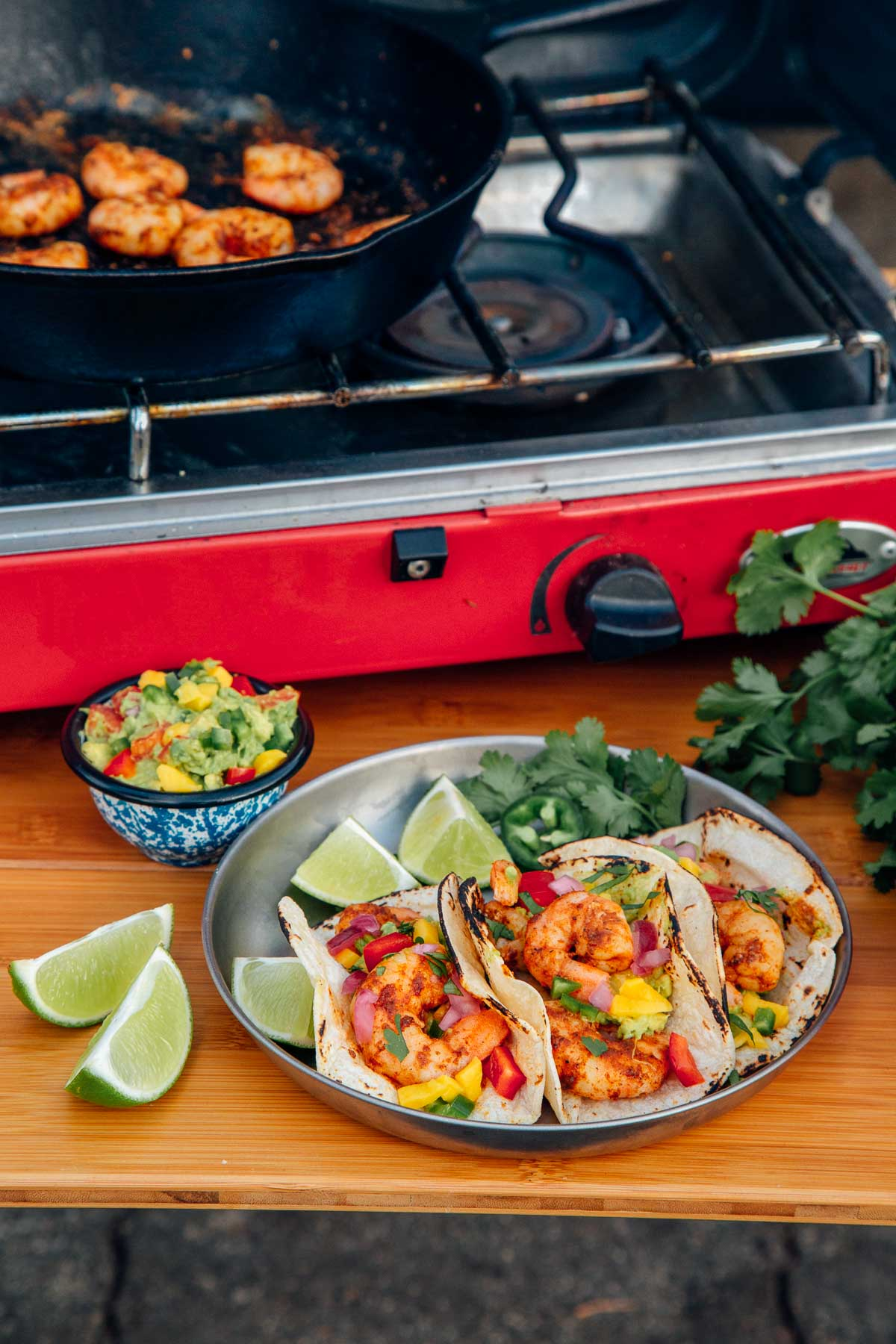 Three shrimp tacos on a silver plate with sliced limes and a small bowl of guacamole on the side. A camp stove is in the background.