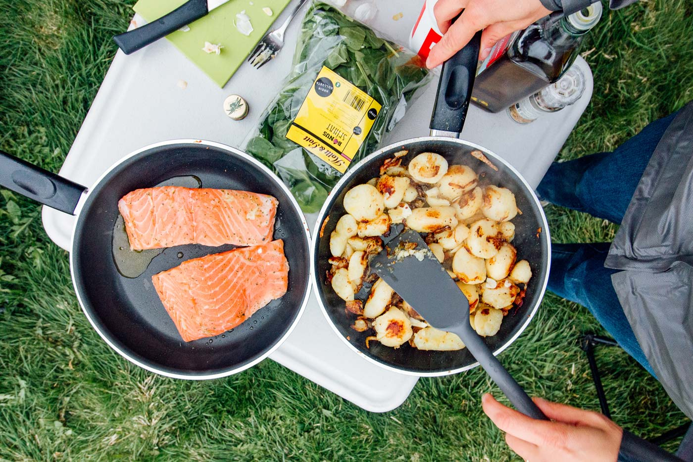 Overhead view of two skillets containing potatoes and salmon on a camping table