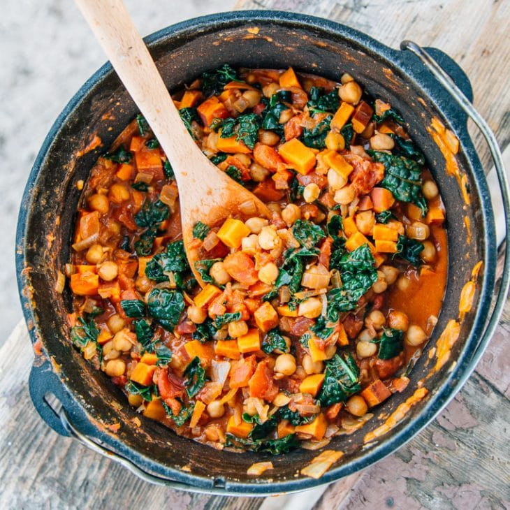 Sweet potato peanut stew in a dutch oven with a wooden spoon