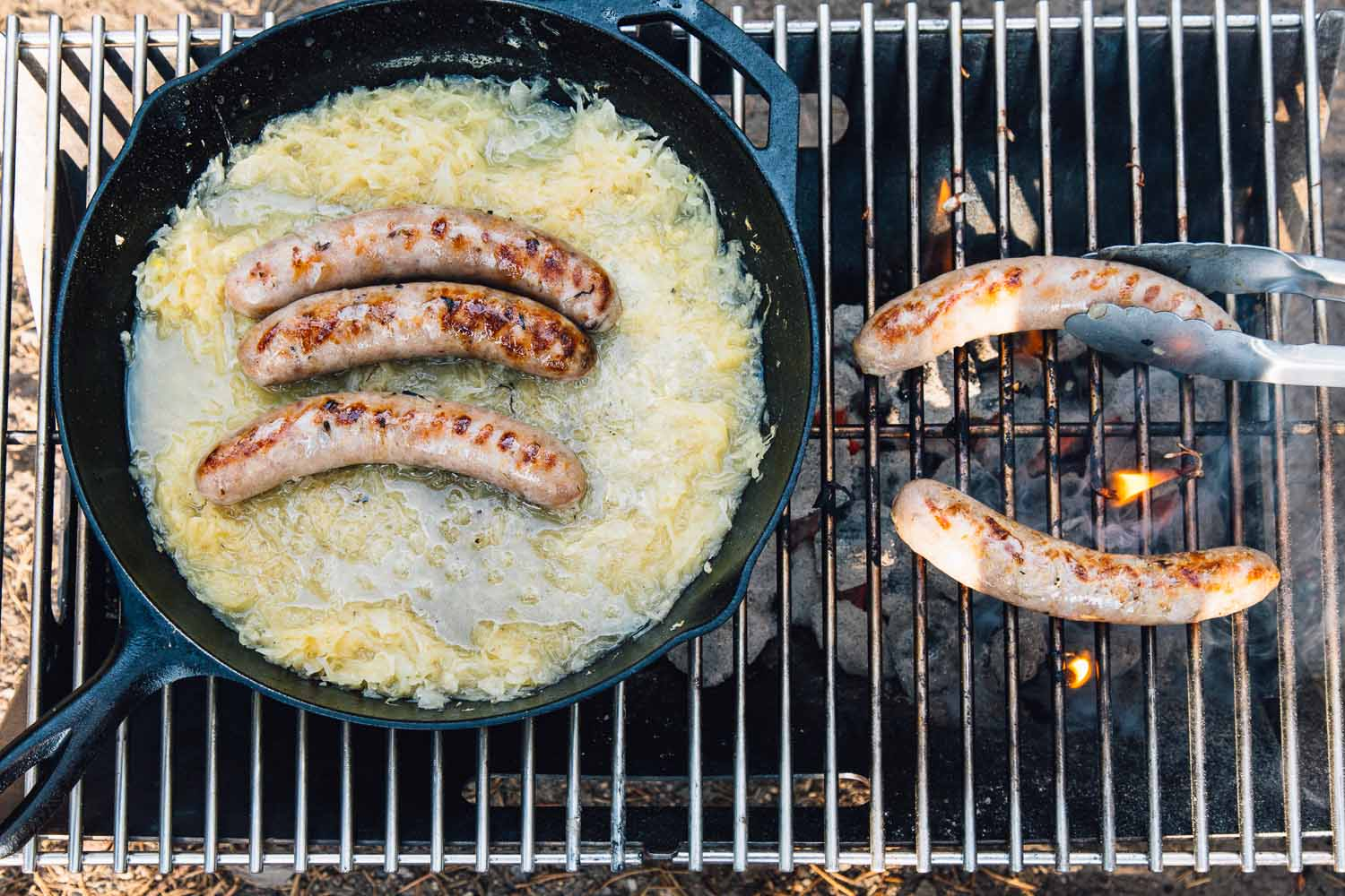 Overhead of a campfire with two beer brats on the grill and three beer brats simmering in beer and sauerkraut