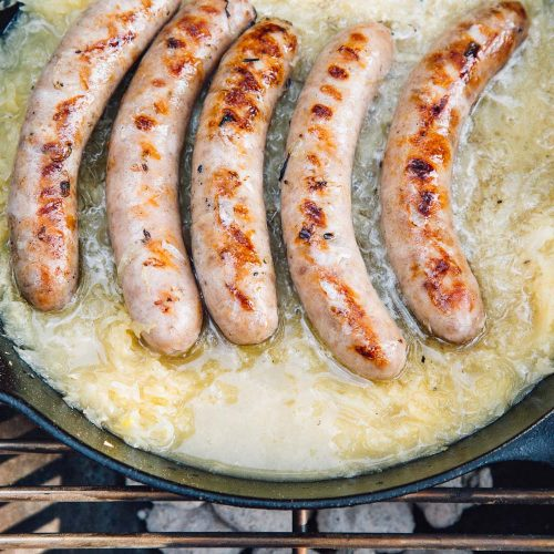 Beer brats simmering in beer and sauerkraut in a cast iron skillet